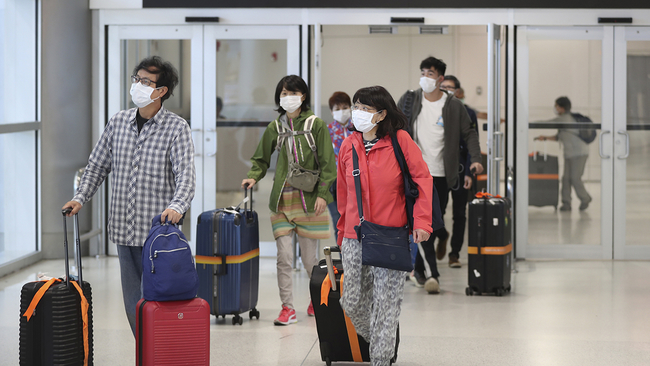 Passengers exit after passing through Customs, Saturday, March 21, 2020, at Miami International Airport in Miami. The airport is one of only 13 airports in the country allowing inbound flights from Europe. (AP Photo/Wilfredo Lee)
